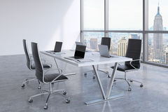 Modern meeting room with huge windows looking at New York City. Black leather chairs and a white table with laptops. Stock Image