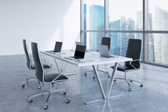 Modern meeting room with huge windows looking at Singapore business city. Black leather chairs and a white table with laptops. Stock Images