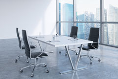 Modern meeting room with huge windows looking at Singapore business city. Black leather chairs and a white table with laptops. Royalty Free Stock Photos