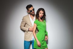Modern man behind sexy woman in green dress posing. Modern men behind sexy women in green dress posing together as lovers in studio Stock Photo