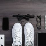 Modern men fashion accessories and electronic devices on dark background. White sneakers, tablet and phone flat lay. Modern men fashion accessories and royalty free stock photos