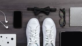 Modern men fashion accessories and electronic devices on dark background. White sneakers, tablet and phone flat lay. Modern men fashion accessories and stock images