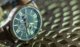 Modern men`s watch, brown-gold color in close up shot. With brown texture Royalty Free Stock Image