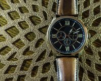 Modern men`s watch, brown-gold color in close up shot. With brown texture Royalty Free Stock Photo