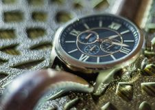 Modern men`s watch, brown-gold color in close up shot. With brown texture Stock Image