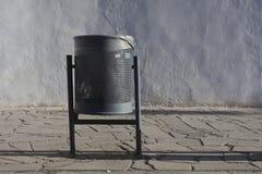 Modern Metallic trash bin in a urban environment. Modern Metallic trash bin in a sunny urban environment Royalty Free Stock Photo