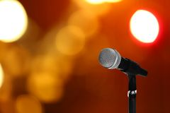 Modern microphone on stand against blurred background. Space for text stock photography