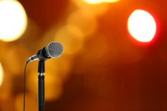Modern microphone on stand against blurred background. Space for text royalty free stock photo