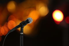 Modern microphone on stand against blurred background. Space for text stock photo