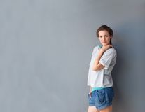 Modern mid adult woman posing against gray background Stock Photos