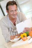 Modern middle aged man cooking with a help of his tablet Royalty Free Stock Image