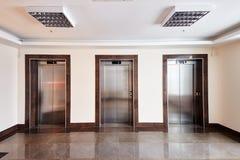 Modern minimalist business centre lobby interior with three closed steel lift doors.  stock photos