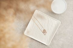 Modern minimalist geometric golden necklace on white marble plate. Necklace in the form of three triangles.