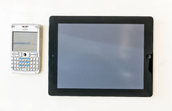 Modern minnestavla och gammal QWERTY smartphone ovanför den finansiella Tiden Fotografering för Bildbyråer