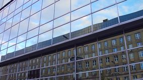 Modern mirror glass office building reflections. Old and new, modern and obsolete concepts. 4K steadicam shot stock footage