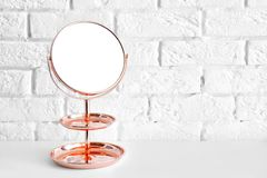 Modern mirror on table. Near brick wall stock image