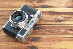 Modern mirrorless camera stilized to retro vintage film camera. On wood table background. 3d illustration Stock Photo