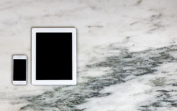 Modern mobile communication devices on marble desktop Royalty Free Stock Photography