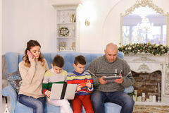 Modern and mobile family, two sons and husband and wife are busy royalty free stock images