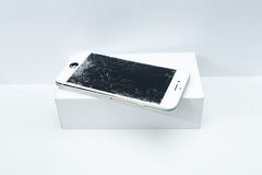 Modern mobile phone with broken screen on white background.  stock image