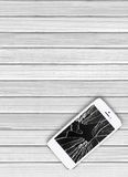 Modern mobile phone with broken screen on white wooden Stock Photography