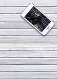 Modern mobile phone with broken screen on white wooden Royalty Free Stock Photos