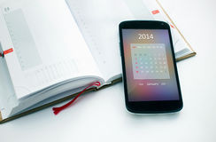 Modern mobile phone with calendar for 2014. Stock Photos