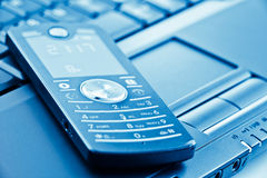 Modern mobile phone on laptop Stock Image