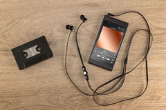 Modern mobile phone and old cassette tape. royalty free stock photo