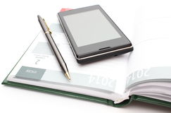 Modern mobile phone and pen lying on open calendar Stock Photography
