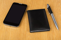 Modern mobile phone with touchscreen, notepad and pen Stock Photos
