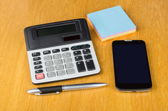 Modern mobile phone with touchscreen, paper, calculator and pen Stock Photos