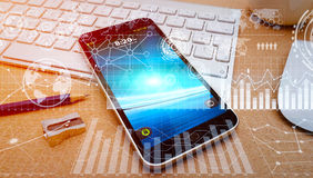 Modern mobile phone whit digital charts and screen interface. Numerous charts, screens and graphics over mobile phone in office Stock Image
