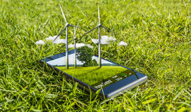 Modern mobile phone and wind turbines in nature as a smartphone- Royalty Free Stock Photos