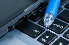 Modern mobiltelefon, blå bollpenna på bärbara datorn Royaltyfria Bilder