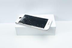Modern mobiltelefon med den brutna skärmen på vit bakgrund Fotografering för Bildbyråer