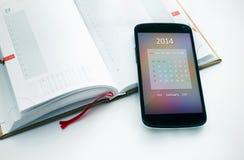 Modern mobiltelefon med kalendern för 2014. Arkivfoton