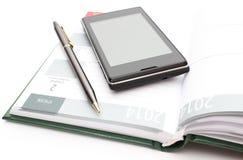 Modern mobiltelefon och penna som ligger på öppen kalender Arkivbild