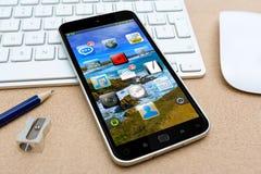 Modern mobiltelefon på en tolkning för skrivbord 3D Royaltyfri Fotografi