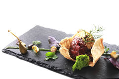 Modern Molecular cuisine. Molecular modern cuisine. Chips Pigskin with tartare or carpaccio of beef. Stock image. Isolated on white Royalty Free Stock Photo