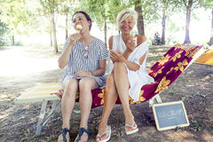 Modern mom and young daughter eating ice cream Royalty Free Stock Image