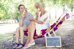 Modern mom and young daughter eating ice cream Royalty Free Stock Images