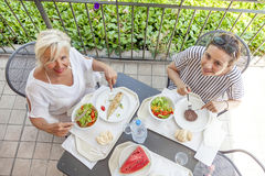 Modern mom and young daughter eating lunch. Sitting at the table in a water park on summertime. Concept of beautiful people having fun in summertime Royalty Free Stock Photo