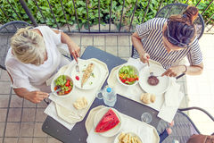 Modern mom and young daughter eating lunch Stock Image