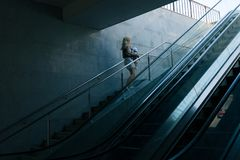 Modern mother with baby toddler in urban passage with dramatic l Royalty Free Stock Images