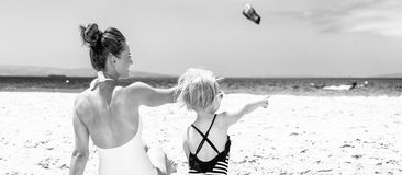 Modern mother and child on beach pointing at something. Family fun on white sand. Seen from behind modern mother and child in beachwear on the beach pointing at royalty free stock photography