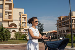 Modern mother on a city street pushing a pram (baby stroller). Royalty Free Stock Images