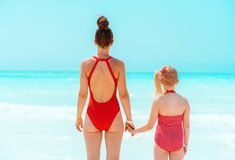 Modern mother and daughter standing on seacoast royalty free stock photography
