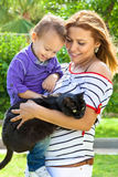Modern mother holding her son and their black cat. Family portrait with a beautiful young modern mother smiling while holding her adorable little son and a funny Stock Photos