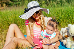 Modern mother sunning with baby on nature Royalty Free Stock Photo